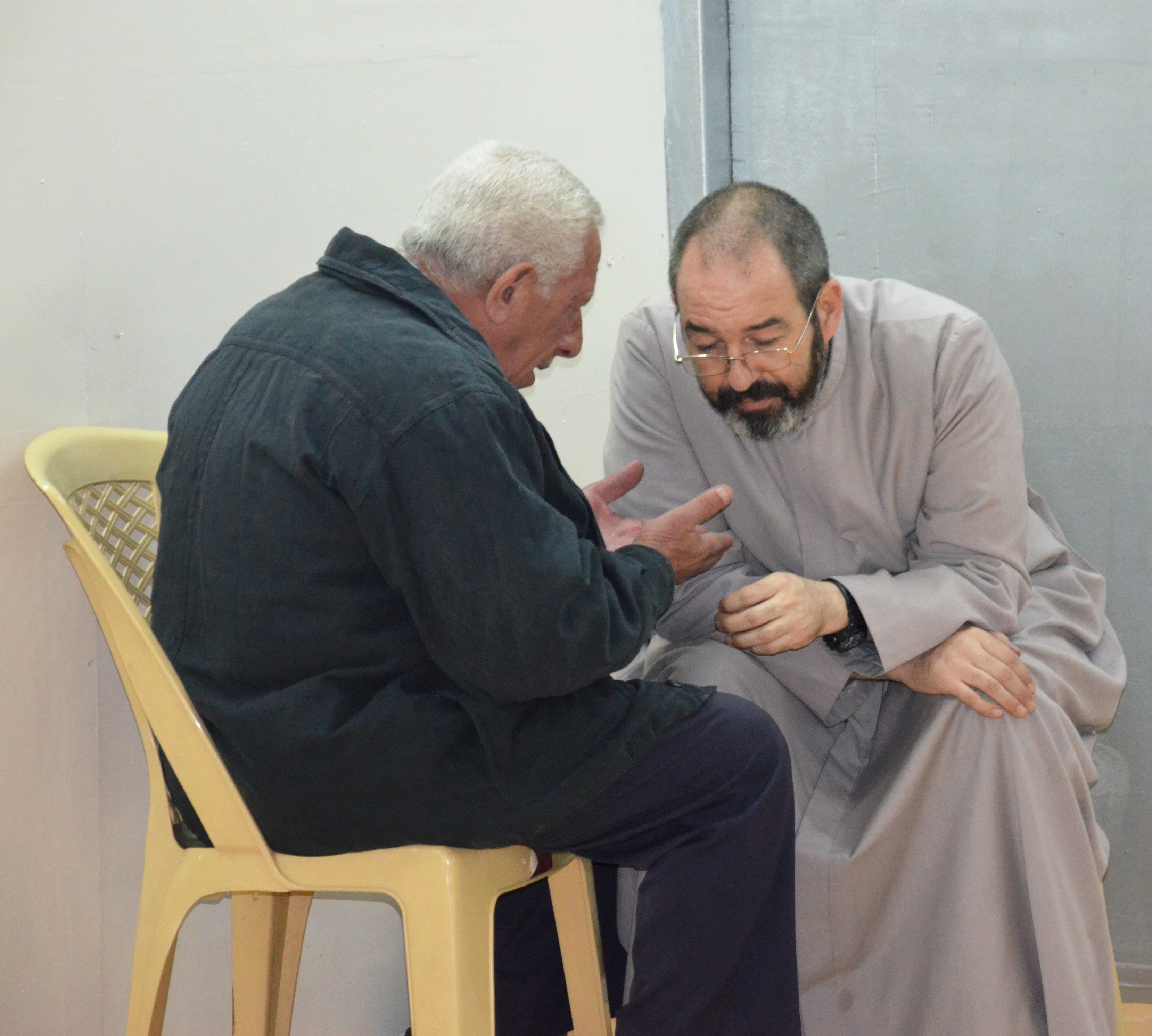 Father Luis Montes hears confession in the back of the new chapel in 'Camp Virgin Mary'