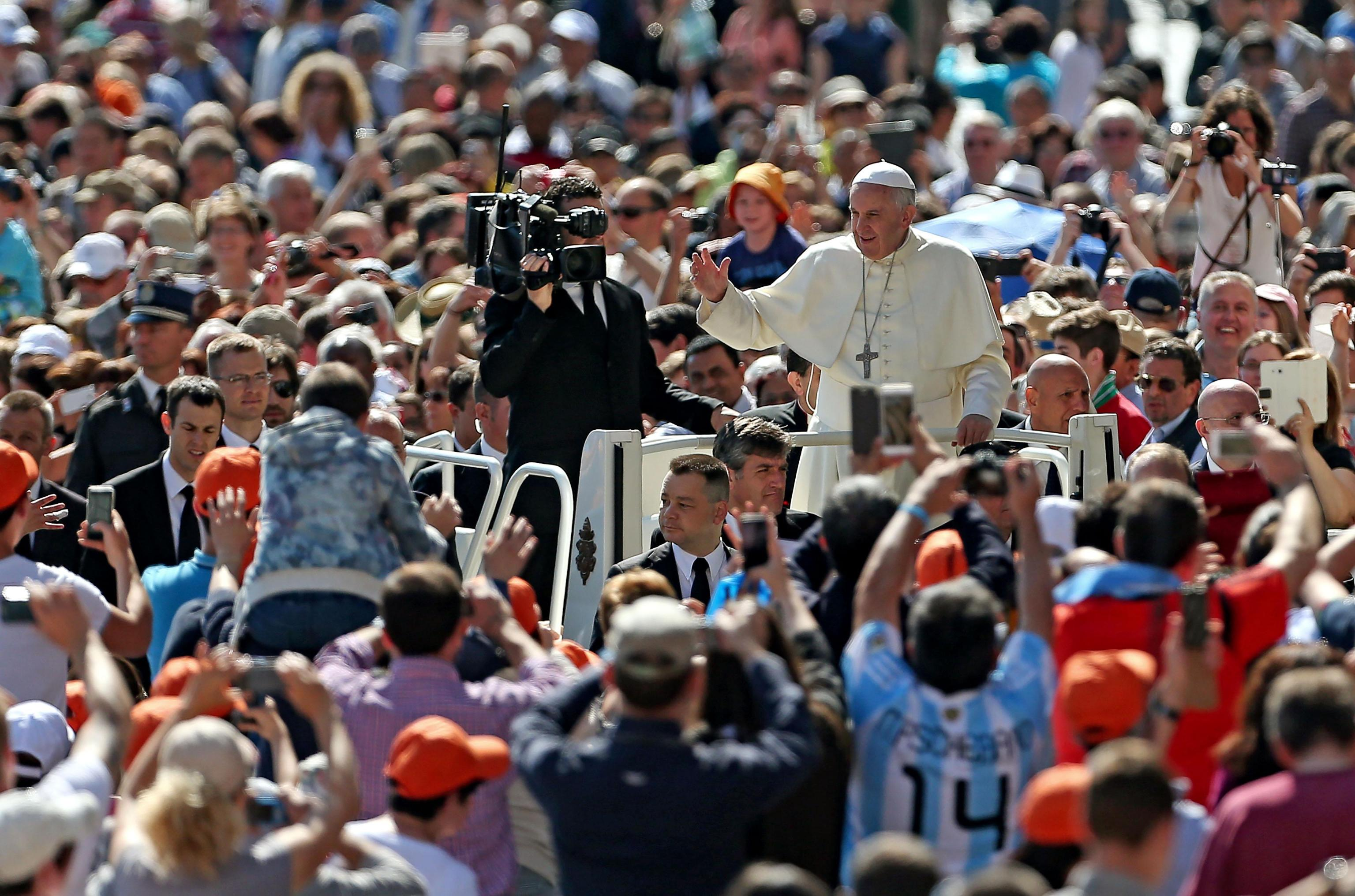 Pope Francis greets the crowd as he arrives for his weekly general audience in St. Peter's Square