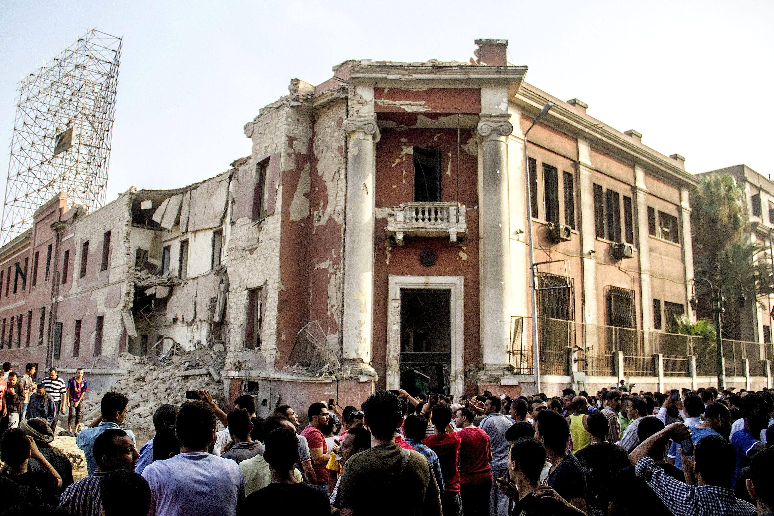 Bystanders at the site following a bomb blast at the Italian Consulate in Cairo
