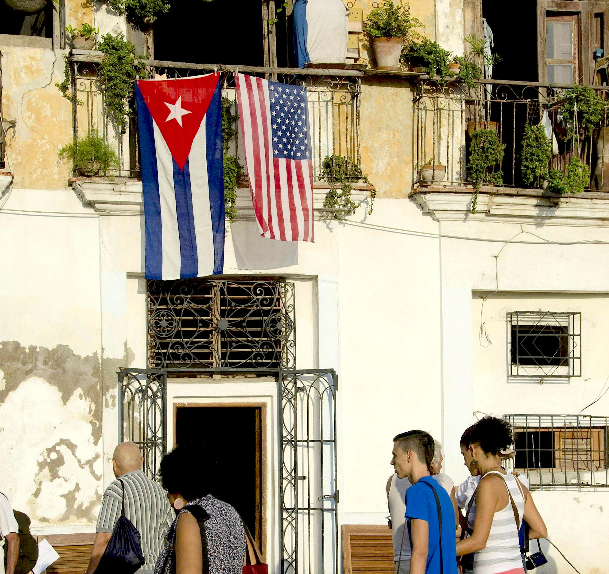 People walk by a balcony with the flags of USA and Cuba in Havana
