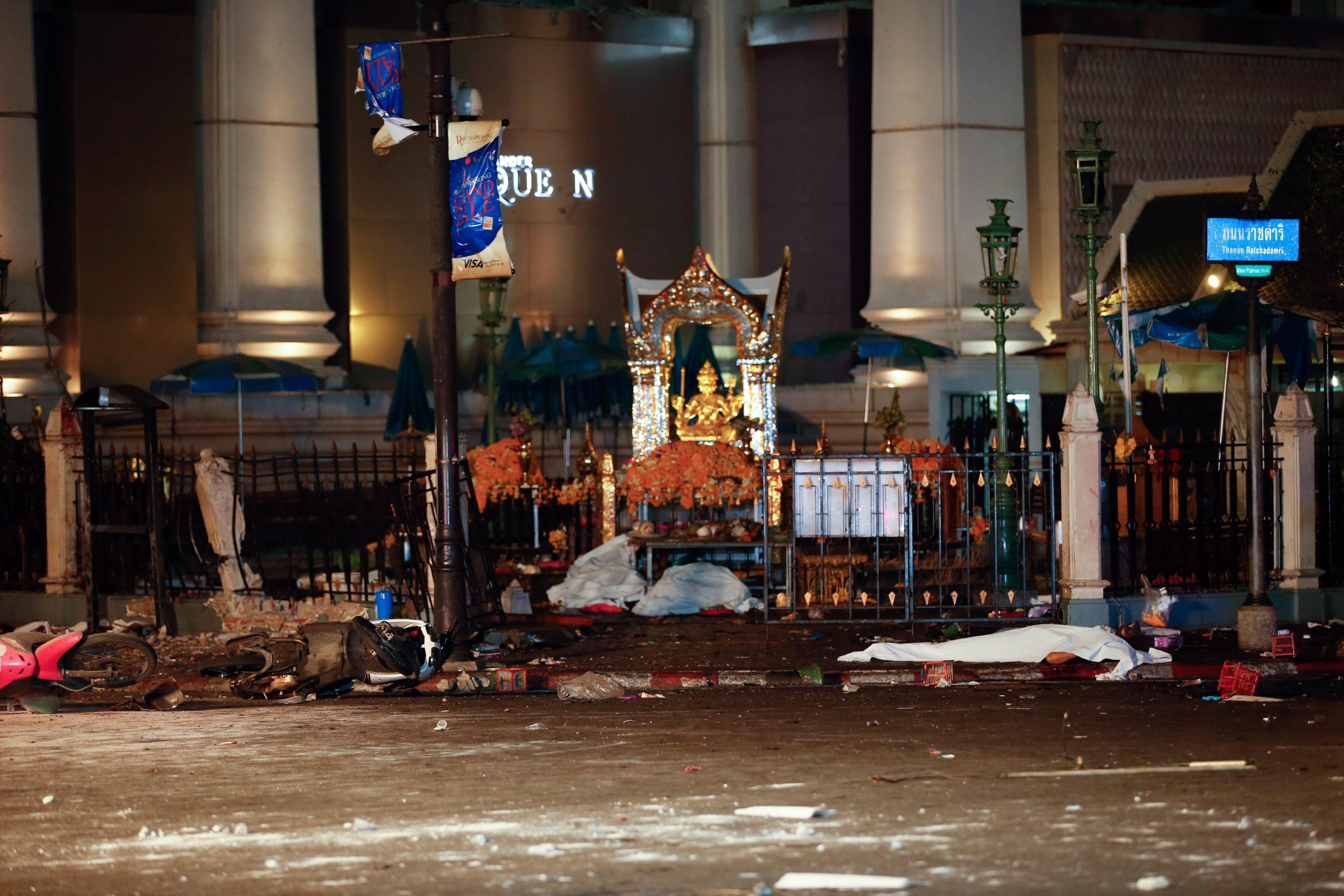 A body lies covered on the ground at the scene of a bomb attack near Erawan Shrine