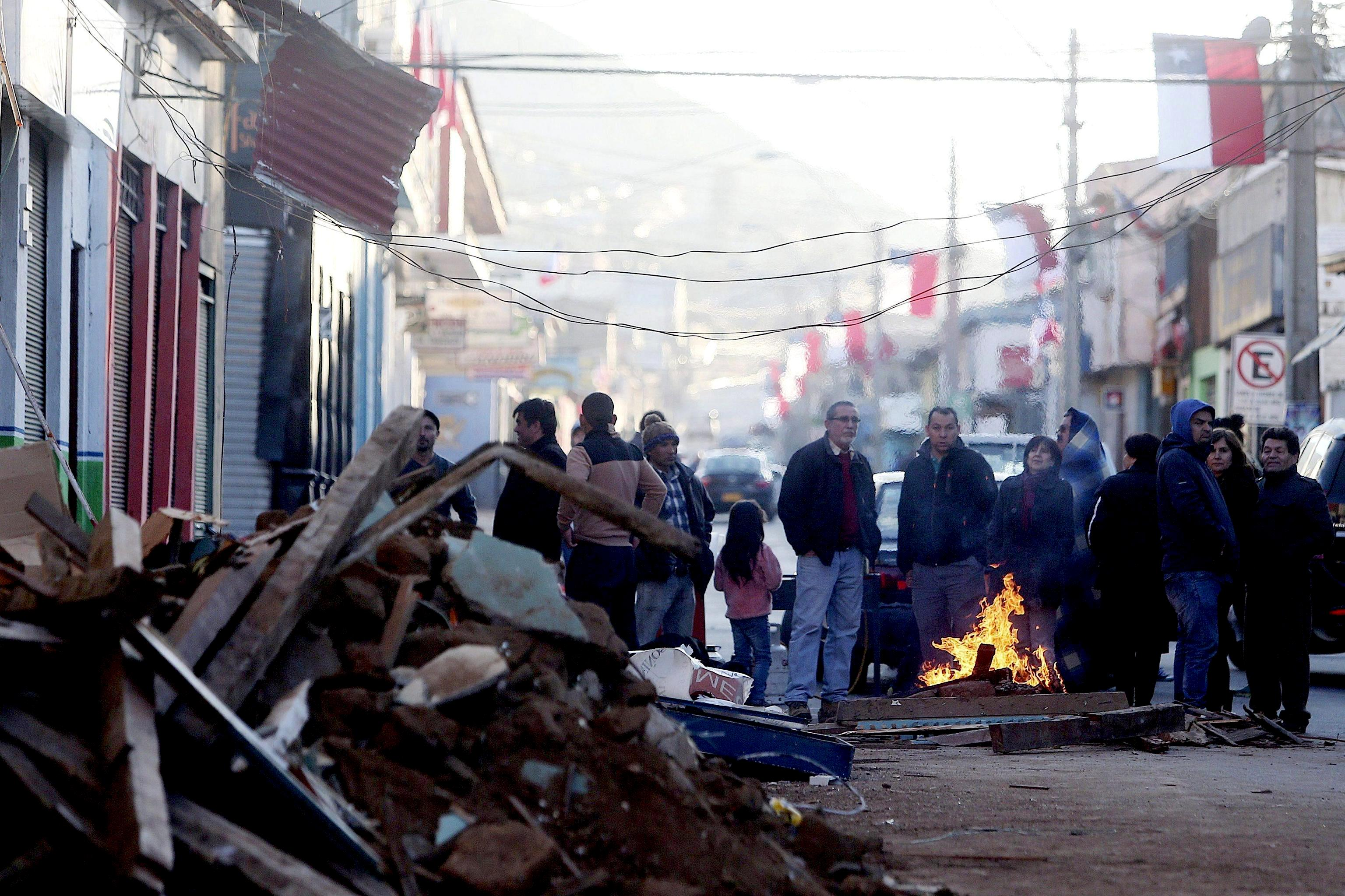 Chileans stand around a fire on a road after being evacuated from their homes following an 8.3 Ritcher scale magnitude earthquake
