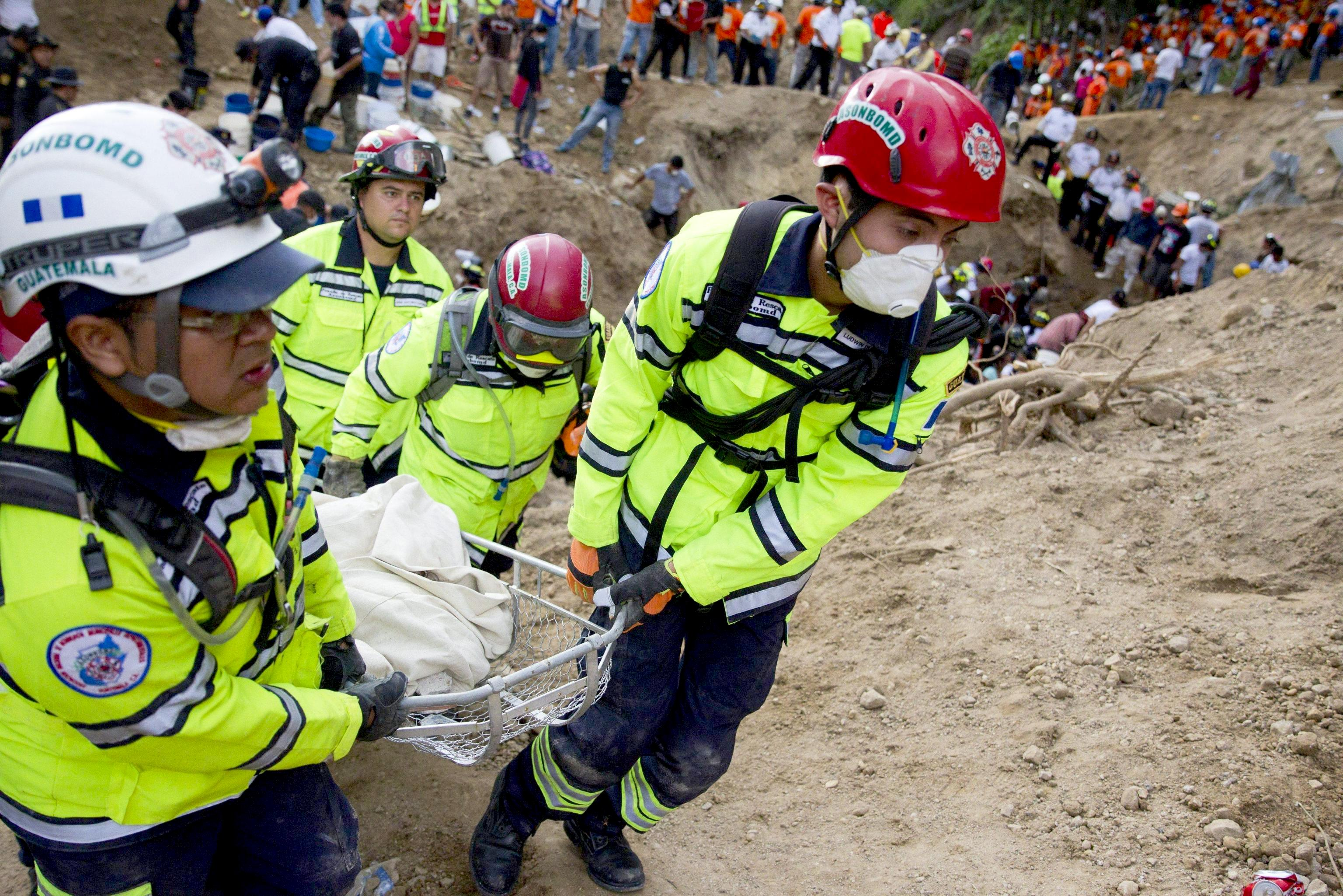 Members of a rescue team recover a body after a landslide in Santa Catarina Pinula municipality