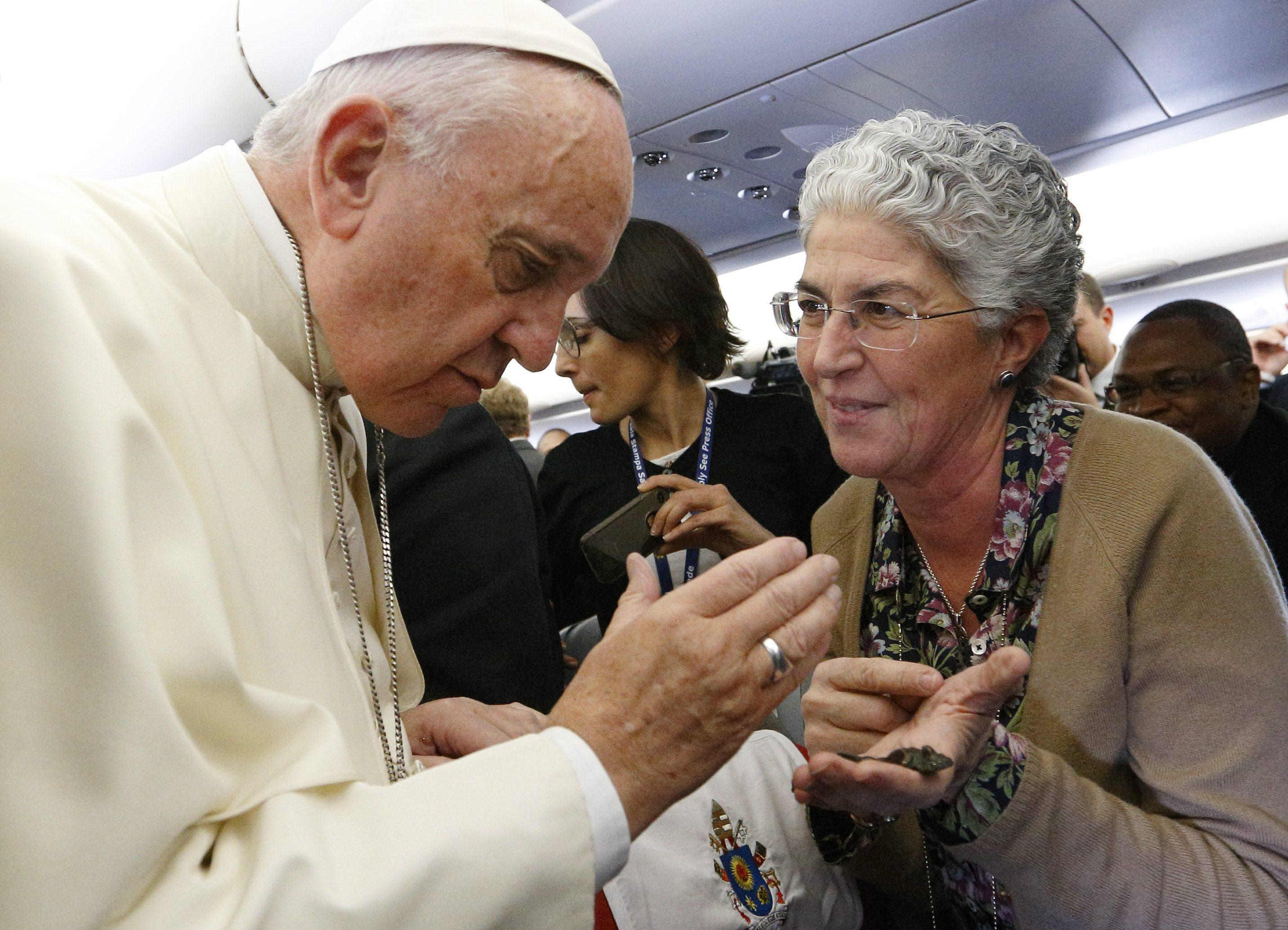 Pope Francis blesses a small sculpture of Jesus Christ presented by Aura Miguel Vistas of Radio Maria Renascenca on his flight from Rome to Nairobi
