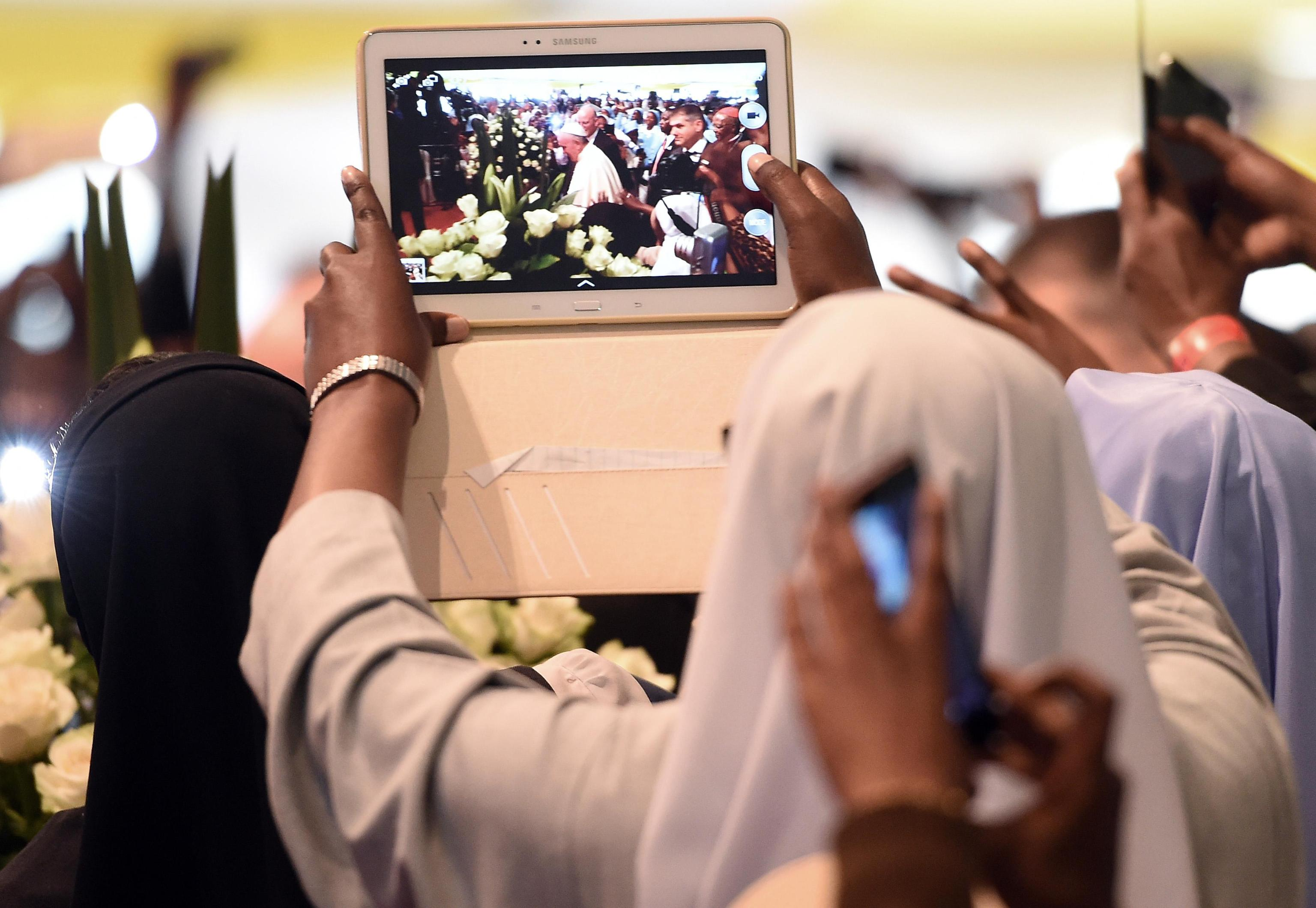 A nun records on a tablet the arrival of Pope Francis at the St. Mary's school to attend a meeting of clergy and religious in Nairobi