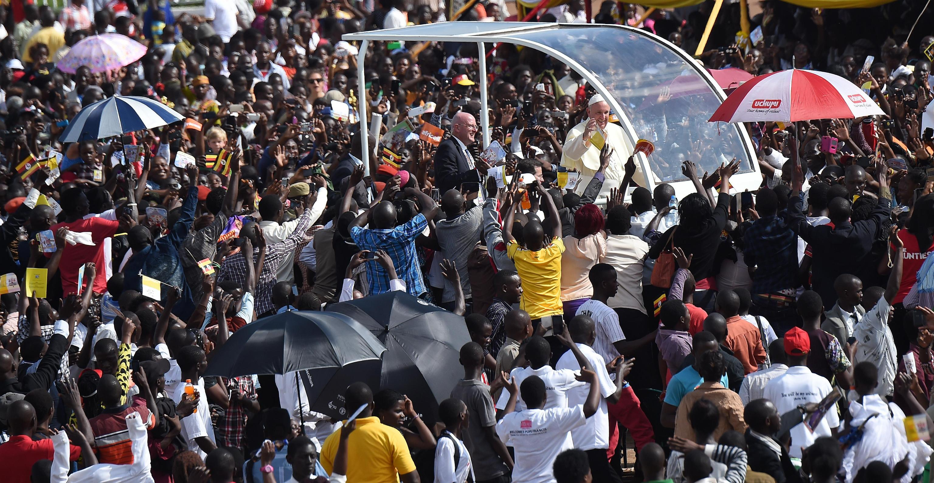 Pope Francis cheers the crowd from the popemobile at his arrival at the meeting with young people at the Kololo airstrip in Kampala