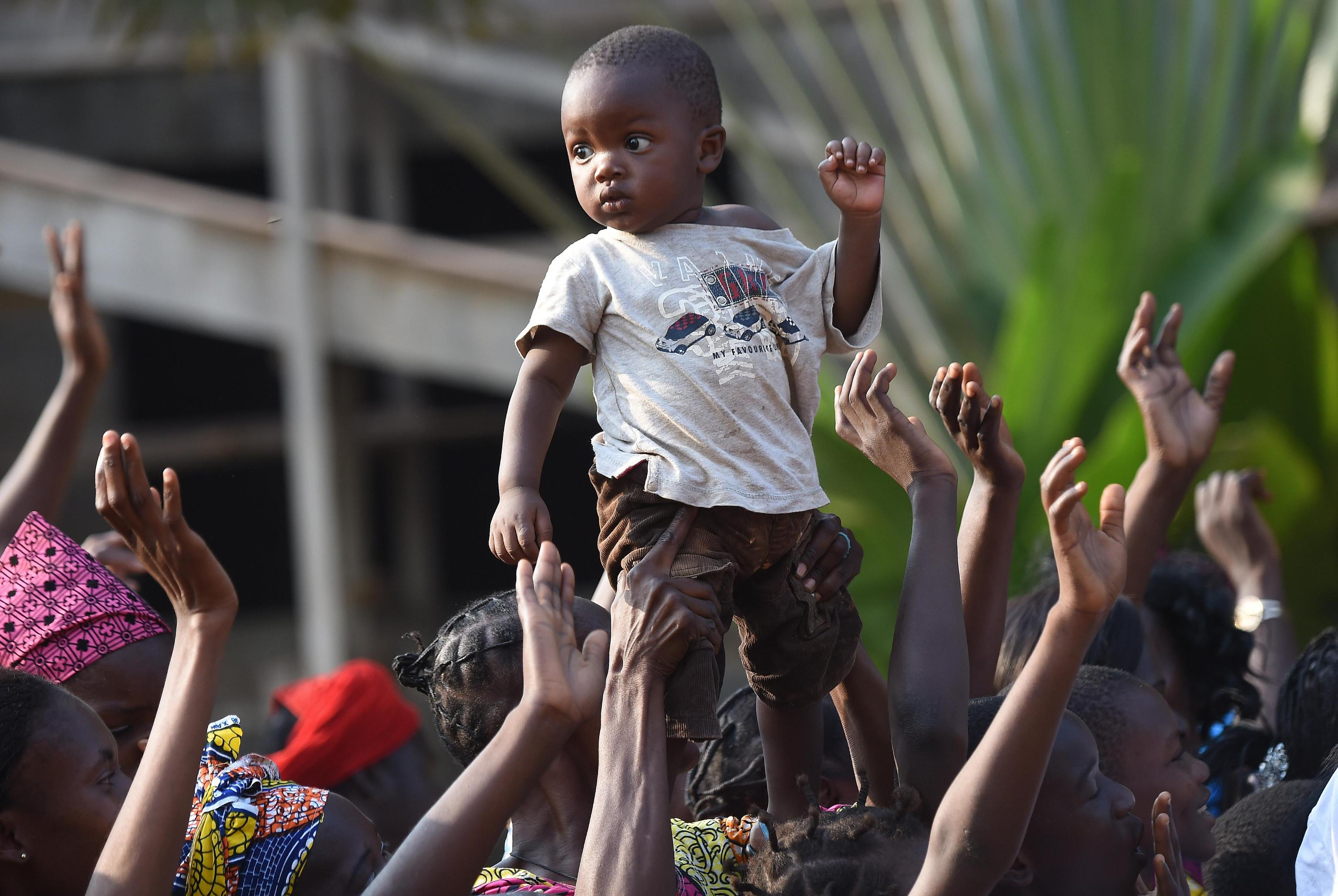 A boy is lifted by her mother at the arrival of Pope Francis at a meeting with evangelical communities at the evangelical theological school in Bangui