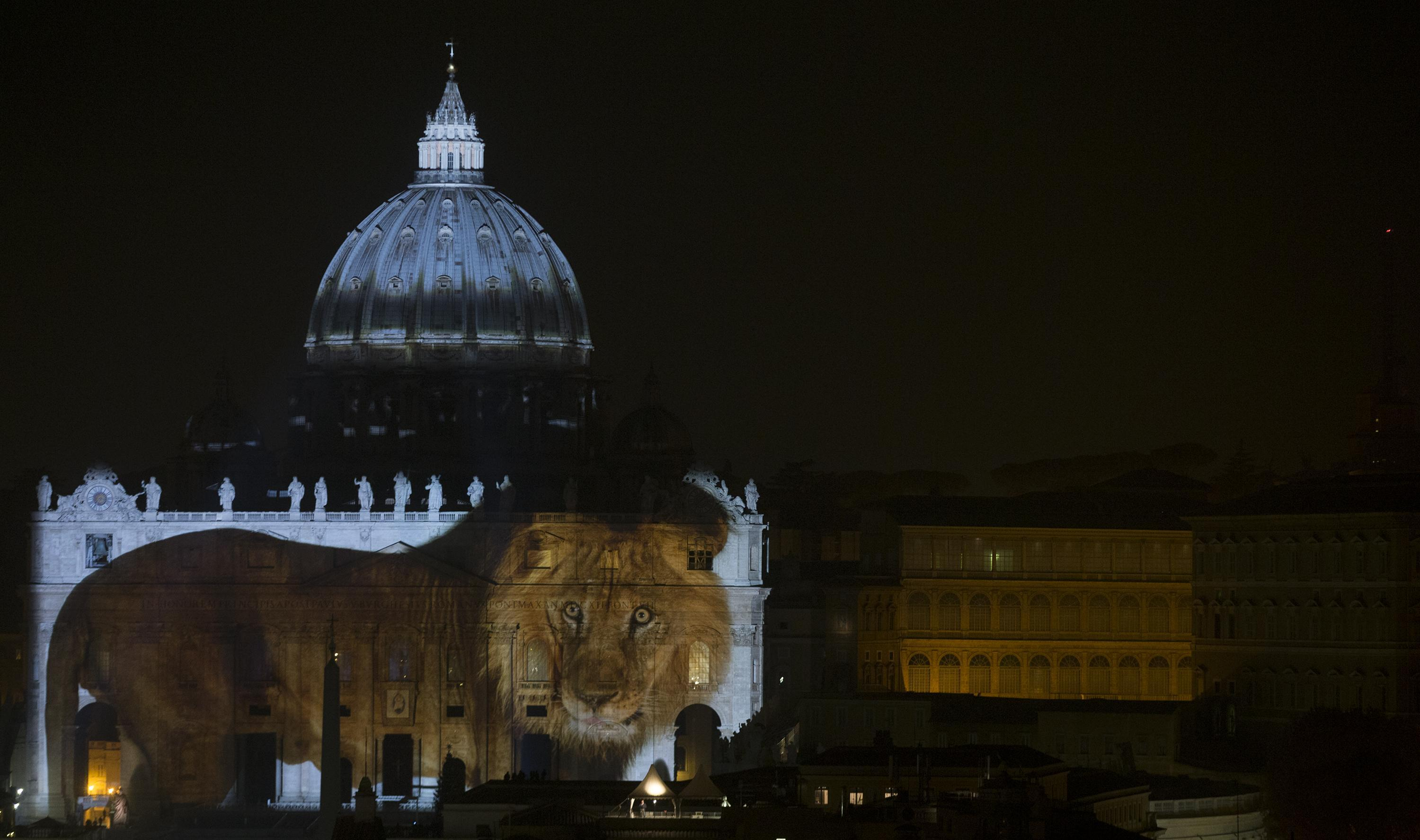The facade of Saint Peter's Basilica illuminated for Fiat Lux event as a tribute for Pope Francis seen from Castel Sant'Angelo