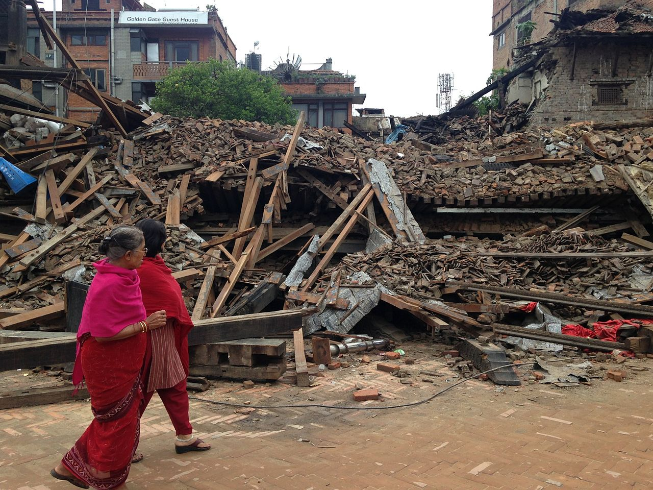 Women walk past buildings destroyed in Bhaktapuin by the April 2015 earthquake in Nepal