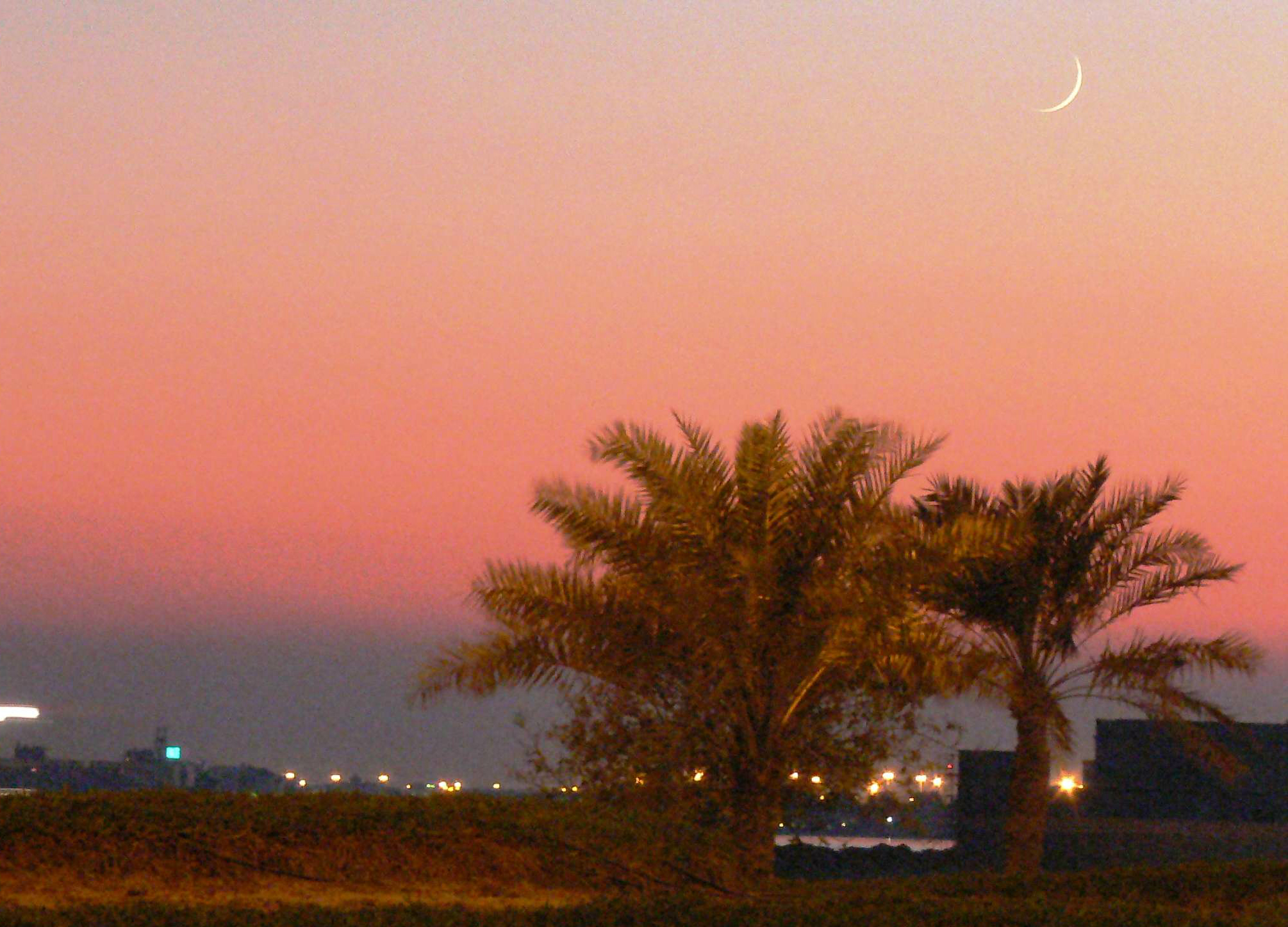 A crescent moon at sunset in Manama