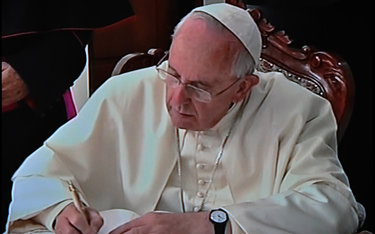Pope Francis signing the Visitors Record Book of the Sanctuary of the Virgen del Quinche